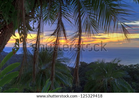 Empty chairs under a plam tree on a poolside 'beach' overlooking the Pacific Ocean and Nicoya Peninsula at sunset near Tarcoles, Costa Rica (HDR) - stock photo