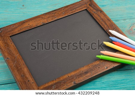 empty chalkboard with copyspace and colorful crayons on wooden table - stock photo