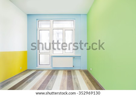 Empty cheerful kids room with green, yellow and blue color walls and wooden flooring after renovation - stock photo