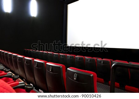 Empty cimema with red seats and white screen - stock photo