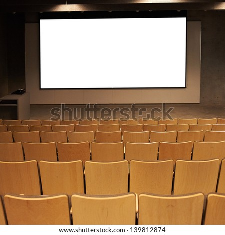 Empty cinema with white isolated screen and brown chairs.