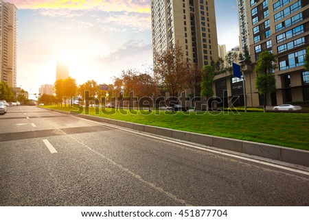 Empty City road surface floor with streetscape buildings of golden yellow sunset - stock photo