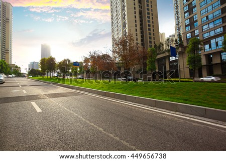 Empty City road surface floor with streetscape buildings of sunset - stock photo