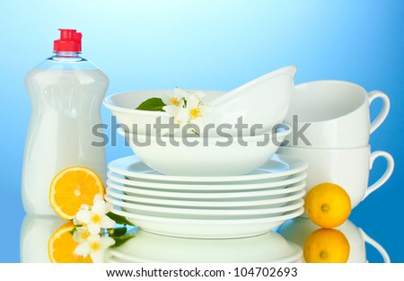 empty clean plates and cups with dishwashing liquid and lemon on blue background
