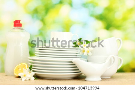 empty clean plates and cups with dishwashing liquid, flowers and lemon on wooden table on green background - stock photo