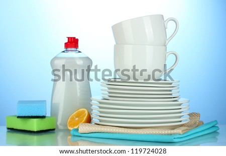 empty clean plates and cups with dishwashing liquid, sponges and lemon on blue background - stock photo