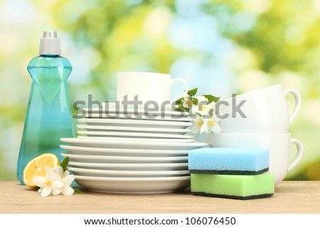 empty clean plates and cups with dishwashing liquid, sponges and lemon on wooden table on green background