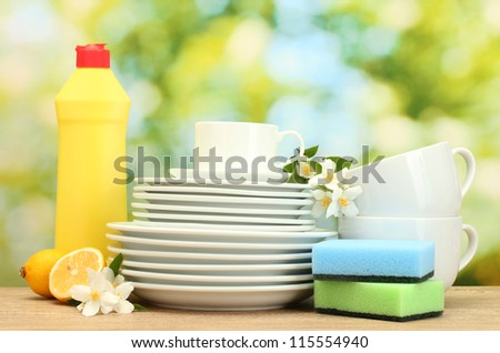 empty clean plates and cups with dishwashing liquid, sponges and lemon on wooden table on green background - stock photo