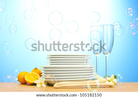 empty clean plates and glasses and lemon on wooden table on blue background - stock photo