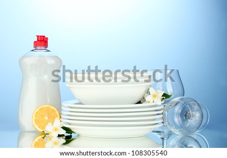 empty clean plates and glasses with dishwashing liquid and lemon on blue background - stock photo