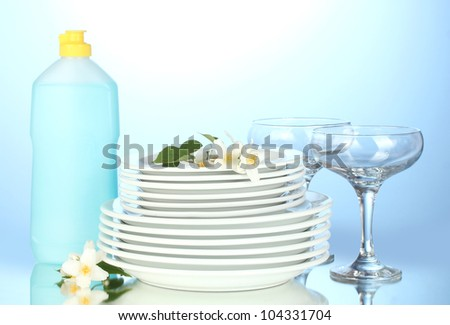 empty clean plates and glasses with dishwashing liquid on blue background - stock photo