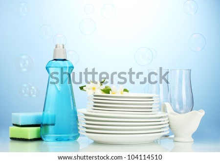 empty clean plates and glasses with dishwashing liquid, sponges and flowers on blue background - stock photo