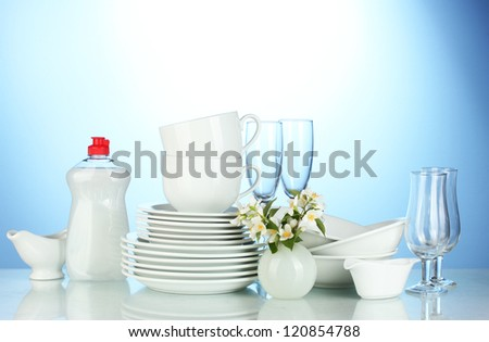 empty clean plates, glasses and cups with dishwashing liquid and flowers on blue background - stock photo