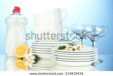 empty clean plates, glasses and cups with dishwashing liquid and lemon on blue background - stock photo