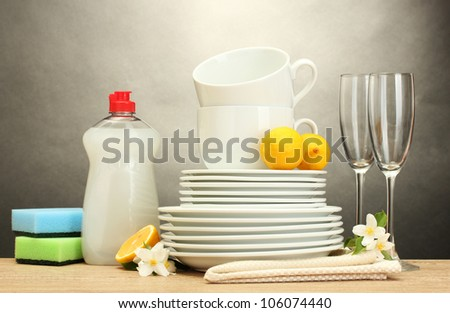 empty clean plates, glasses and cups with dishwashing liquid, sponges and lemon on wooden table on grey background - stock photo