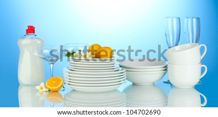 empty clean plates, glasses and cups with dishwashing liquidand lemon on blue background - stock photo