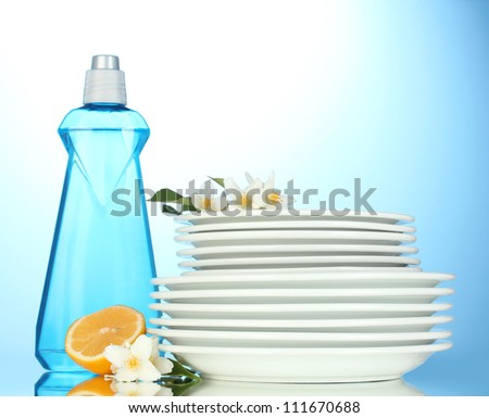 empty clean plates with dishwashing liquid and lemon on blue background - stock photo