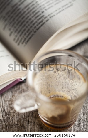 Empty coffee cup on a wooden background with a book - stock photo