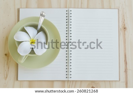 Empty coffee cup with flower and notebook on wood table - stock photo