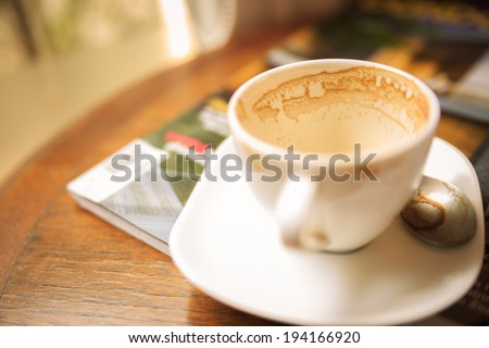 Empty coffee cup wood Magazine read morning,beautyful light,empty coffee have spoon beside on the desk ,have a Magazine can read in the morning,beautyful light - stock photo