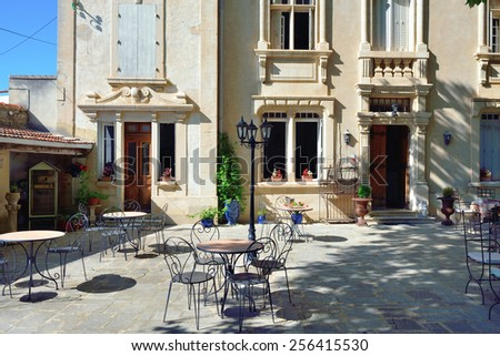 Empty coffee terrace with tables and chairs, Provence, France - stock photo