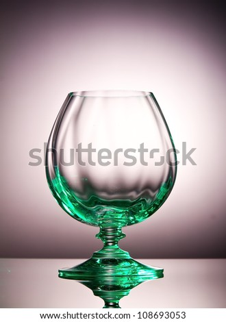 Empty cognac glass with a green tint on a shiny surface