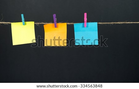 Empty colored paper notes hanging on a rope attached with pegs on a black background
