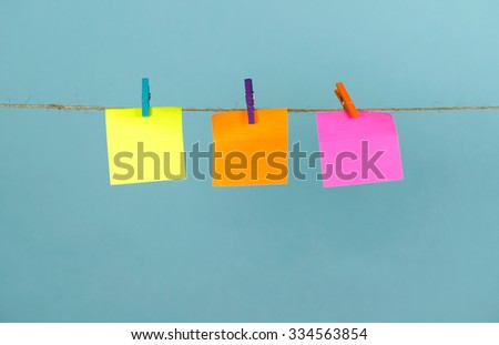 Empty colored paper notes hanging on a rope attached with pegs on a blue background