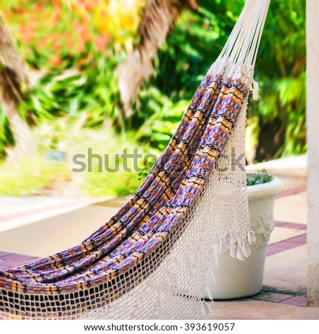 Empty colorful cloth and rope hammock hanging by the garden patio square composition