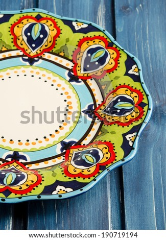 Empty colorful plate on old wooden table - stock photo