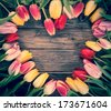Empty colourful heart-shaped frame of fresh tulips arranged on an old rustic wooden background with central copyspace for your Valentines, engagement, of anniversary message to a loved one - stock photo