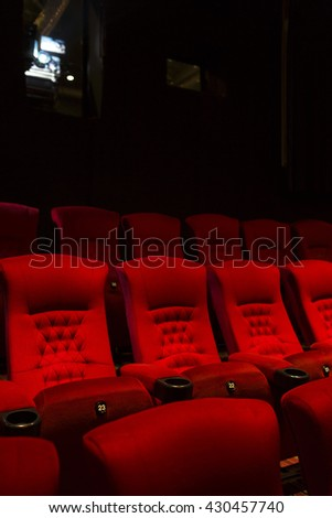Empty comfortable red seats with numbers in cinema