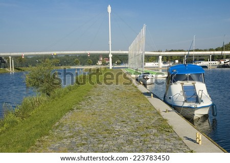 Empty concrete pier on the lakeshore and boats moored in marina, Mazury, Poland - stock photo