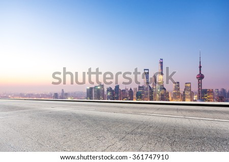 empty concrete road and cityscape in blue sky at dawn - stock photo
