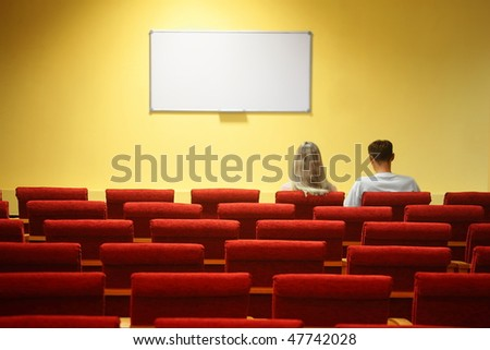 empty conference hall. rows of a chairs. focus on a third row. man and woman sitting in chairs - stock photo