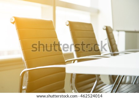 Empty conference table and chairs in meeting room, warm lighting effect