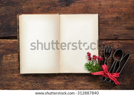 Empty cookbook for Christmas recipes on wooden table - stock photo