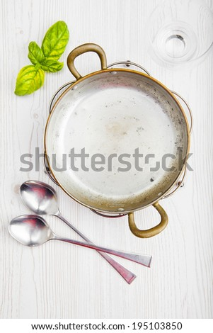 empty cookware. Italian lunch. a small frying pan, glass and fresh basil leaf. white background. spoon. - stock photo
