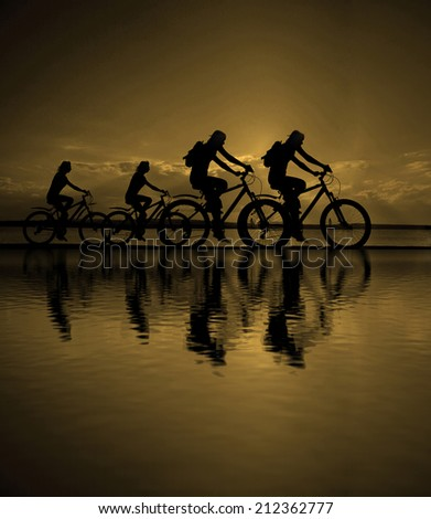 Empty Copy Space for inscription Image of sporty company friends on bicycles outdoors against sunset Silhouette four 4 cyclist going along shoreline coast Reflection sun on water