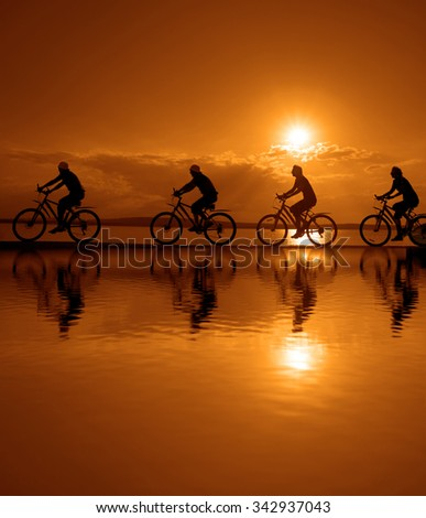 Empty Copy Space Sporty company friends on bicycles outdoors against sunset Silhouette four 4 cyclist going along shoreline coast Reflection sun on water Sport in Nature background Group of people