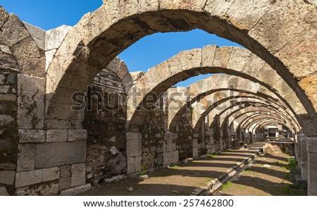 Empty corridor with arcs and blue sky. Ruins of Ancient city Smyrna. Izmir, Turkey - stock photo