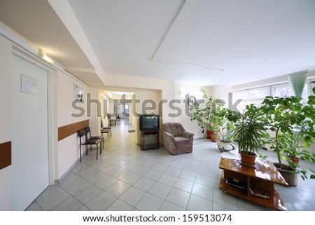 Empty corridor with plants growing in pots, a sofa and chairs - stock photo
