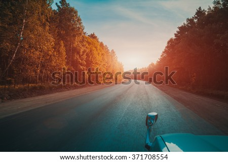 Empty country road, autumn trees, car mirror, view from moving car, vintage color filter - stock photo