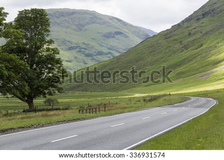 Empty country road through a valley and glen in Glencoe, Highlands of Scotland - stock photo