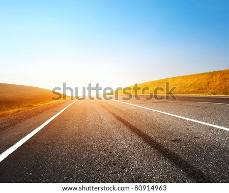 Empty countryside asphalt road and clear blue sky - stock photo