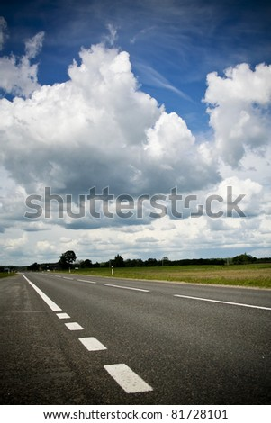 Empty countryside's road with the beautiful clouds and sky above - stock photo