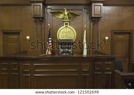 Empty courtroom with chair of judge and flags - stock photo