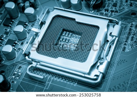Empty CPU processor socket with pins on motherboard toned blue - stock photo