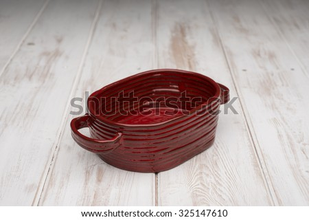 Empty, crimson red, deep rounded rectangular dish and on a white wooden panel surface.