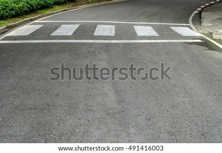Empty crosswalk on asphalt road with red and white sign on sidewalk curb